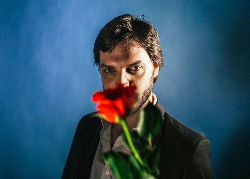 portrait of Tom Hogan holding a rose