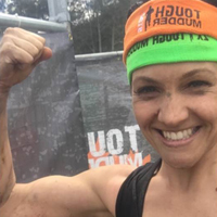 Smiling woman wearing Tough Mudder headband and flexing her arm muscles