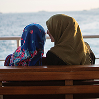 Two women wearing head scarves talking on a seat in front of the ocean