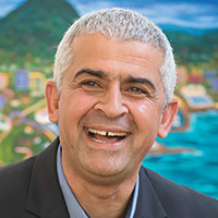Smiling man with short grey hair in front of colourful landscape painting