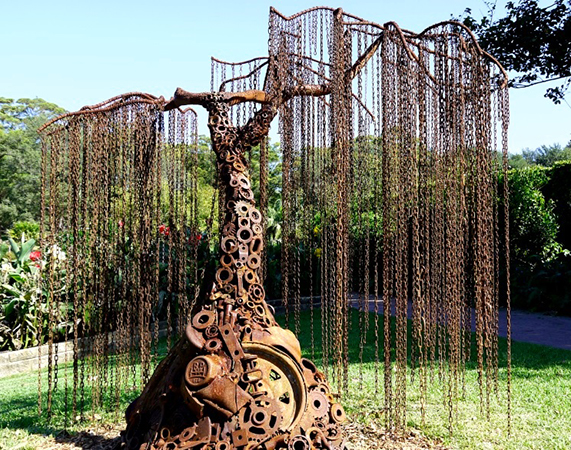 Sculpture by Mike Tikkeros in the shape of a weeping willow tree made from rusted metal parts