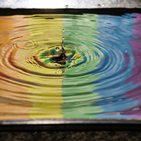 Puddle of water with drop in centre, and reflection of a rainbow